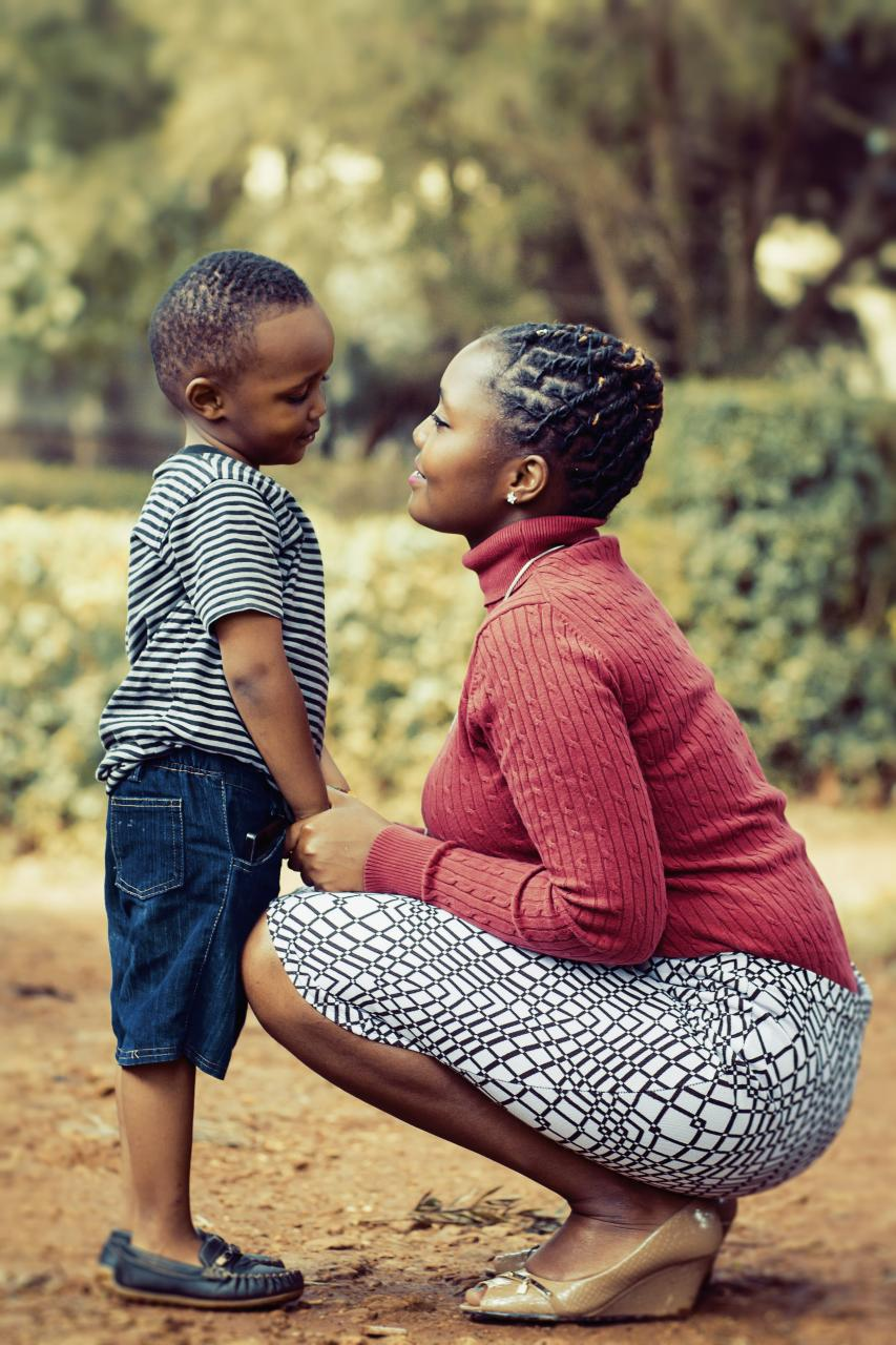 Tilt Shift Lens Photography of Woman Wearing Red Sweater and White Skirt While Holding a Boy Wearing White and Black Crew-neck Shirt and Blue Denim Short